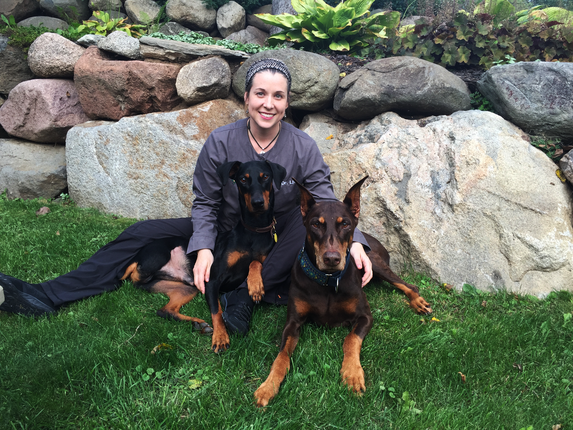 This is a picture of Dr. Liv Kismartoni. She is seen here with two doberman pincers..