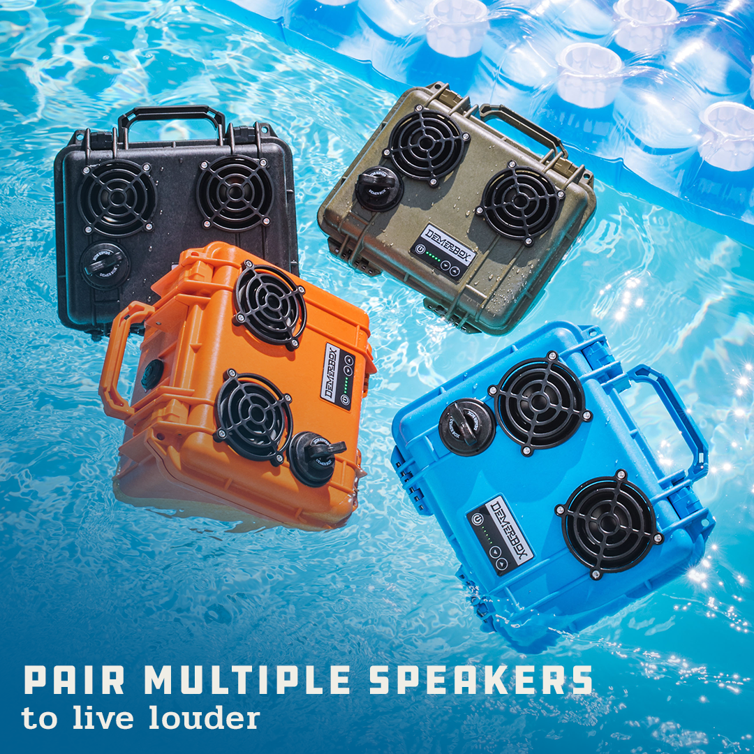 """A collection of floating, waterproof Bluetooth speakers are clustered together in a pool. This collection includes DemerBox DB2s in the following colors: black, green, orange, and blue. Superimposed on the image is the text """"Pair multiple speakers to live louder."""""""