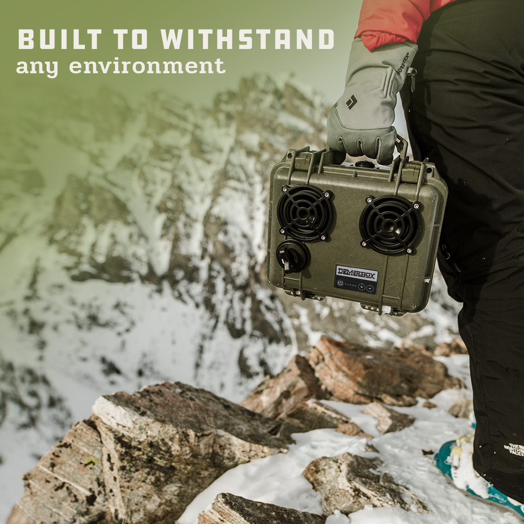 """A person in cold weather gear holding a green DemerBox DB2 in the foreground. In the background there are snow covered mountains. Superimposed on the image is the text """"Built to withstand any environment."""""""
