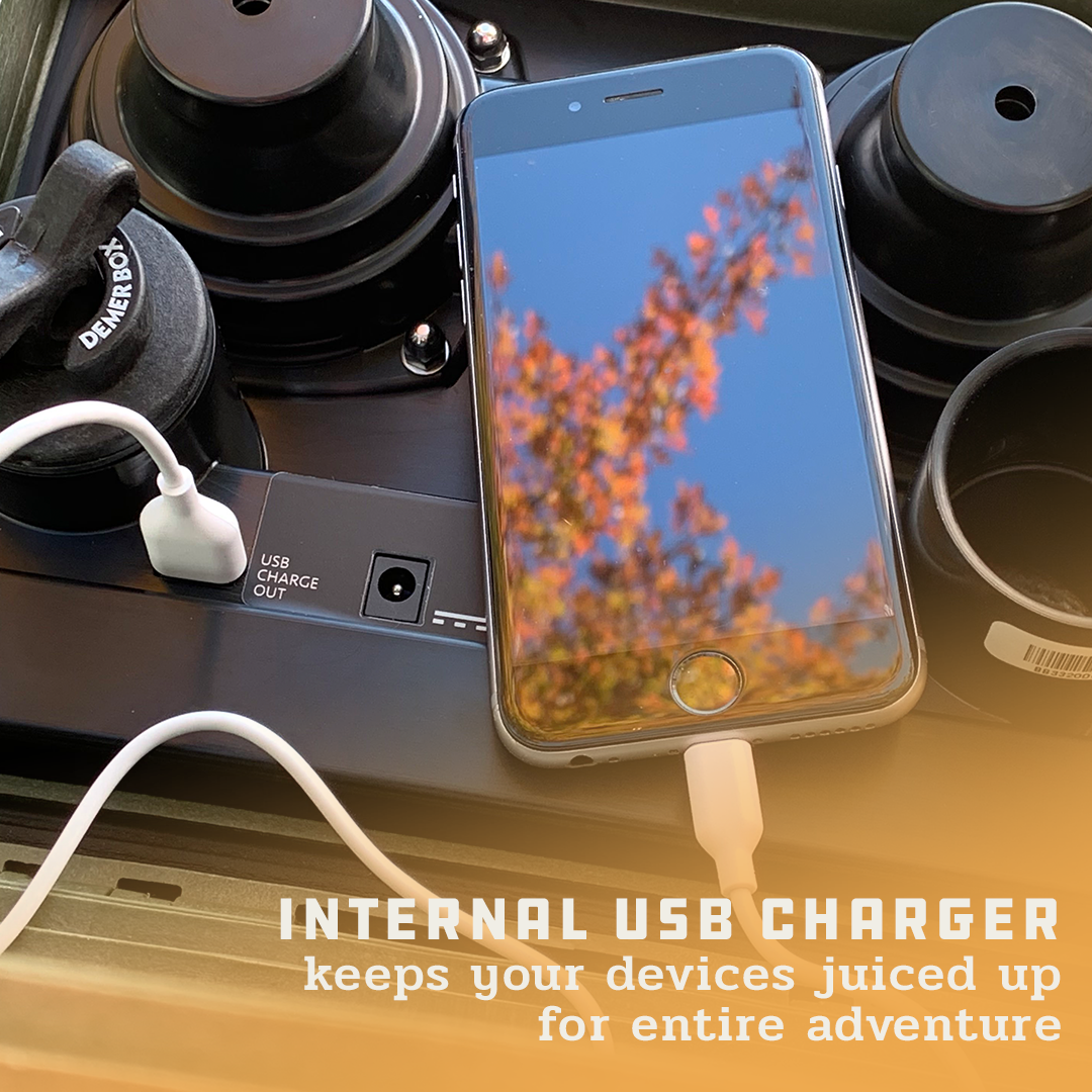 """A close up of the inside of the Demerbox DB2, with a cell phone plugged into the USB charger and the plug port stored next to it. Superimposed on the image is the text """"Internal USB charger keeps your devices juiced up for entire adventure."""""""