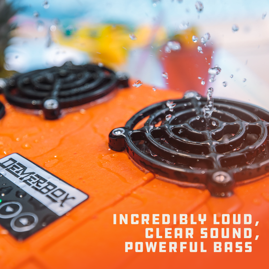 """Droplets of water are vibrating off the speakers of an orange DB2. Superimposed on the image is the text """"Incredibly loud, clear sound, powerful bass."""""""