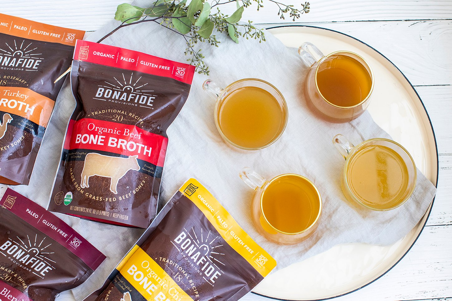 row of three cups of bone broth with organic ingredients