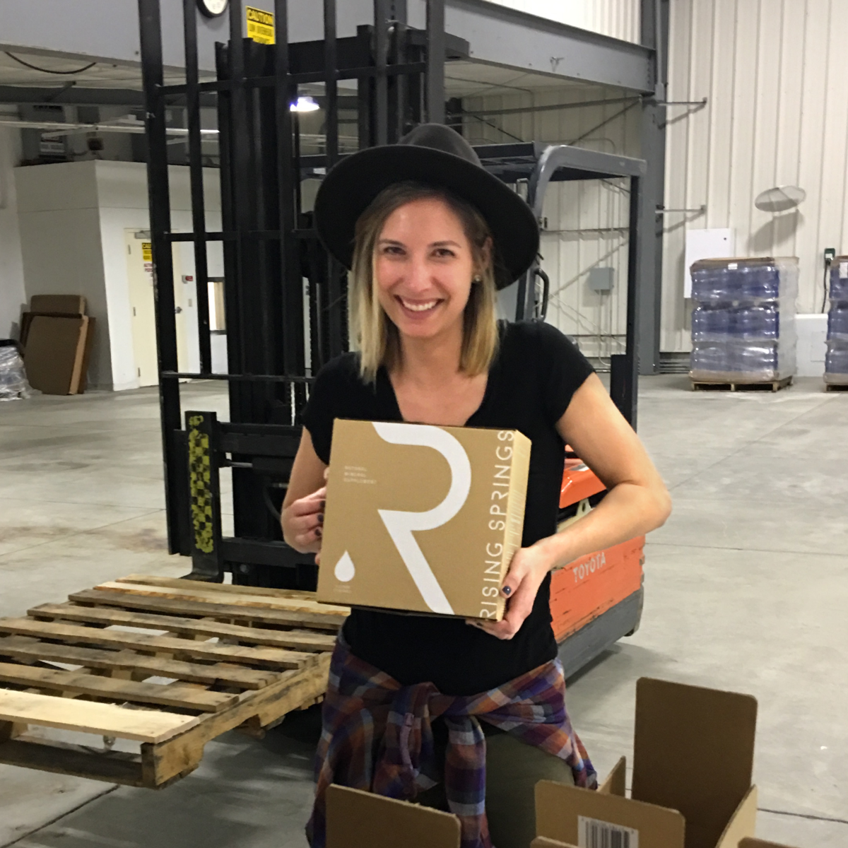 Rising Springs Project Manager holding boxed water