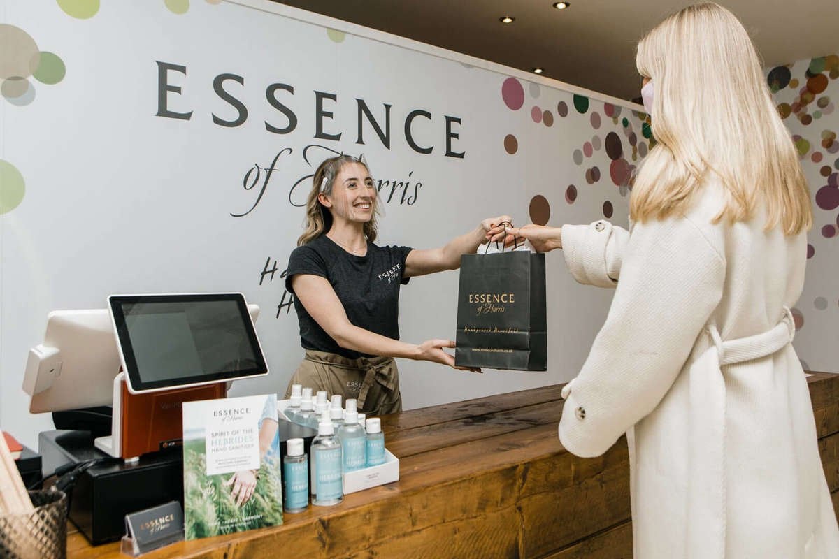 Staff member handing over Essence of Harris products to a customer