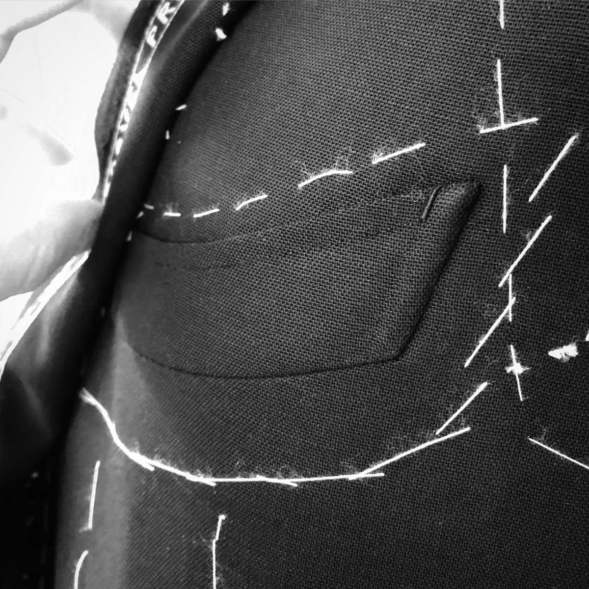 Sartoria Sciarra entirely hand crafted bespoke jacket in progress. Close up of barchetta out breast pocket with hand crafted bar tack and top stitching using Italian silk twist strengthened with bees wax. Made from a bright navy Loro Piana Zelander high twist wool fabric. Luxury bespoke Neapolitan tailoring.