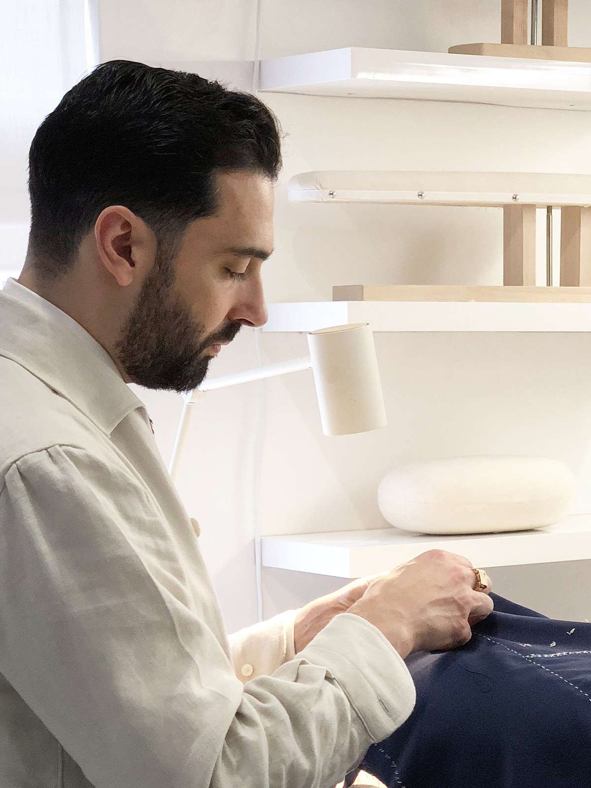 Carl Sciarra director and bespoke tailor at Sartoria Sciarra hand sewing the seams on a bespoke jacket using Italian silk twist strengthened with bees wax. Bespoke suit made from a bright navy Loro Piana Zelander high twist wool fabric. Luxury bespoke Italian tailoring.
