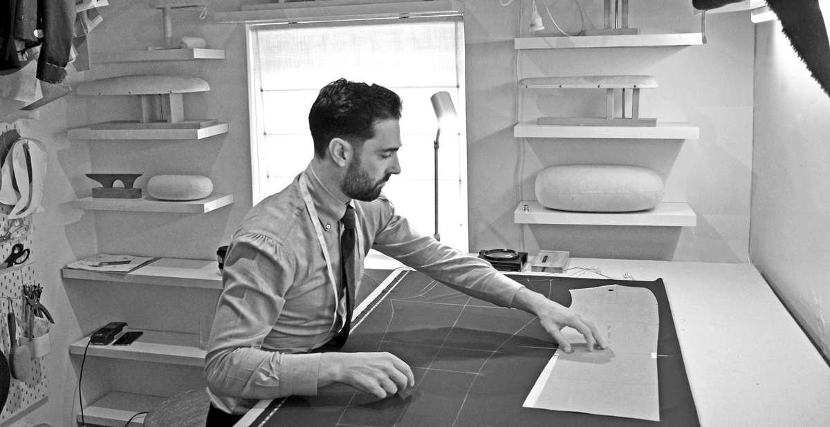 Carl Sciarra director and bespoke tailor at Sartoria Sciarra in the work room chalking a bespoke suit onto Loro Piana Zelander high twist wool. Cotton cashmere bespoke shirt with manica mappina and Italian roll button down collar, shantung silk grenadine tie with a hand rolled tip. Tailors pressing boards and hams, Tailors tool board.