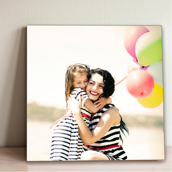 Tile photo of a mother hugging little girl with balloons in the background
