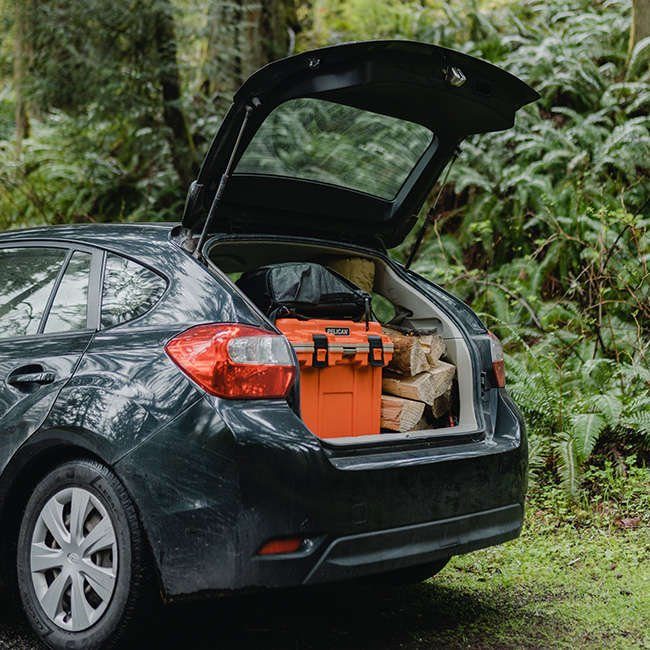 A Pelican Elite Cooler packed in a car with firewood and camping gear.