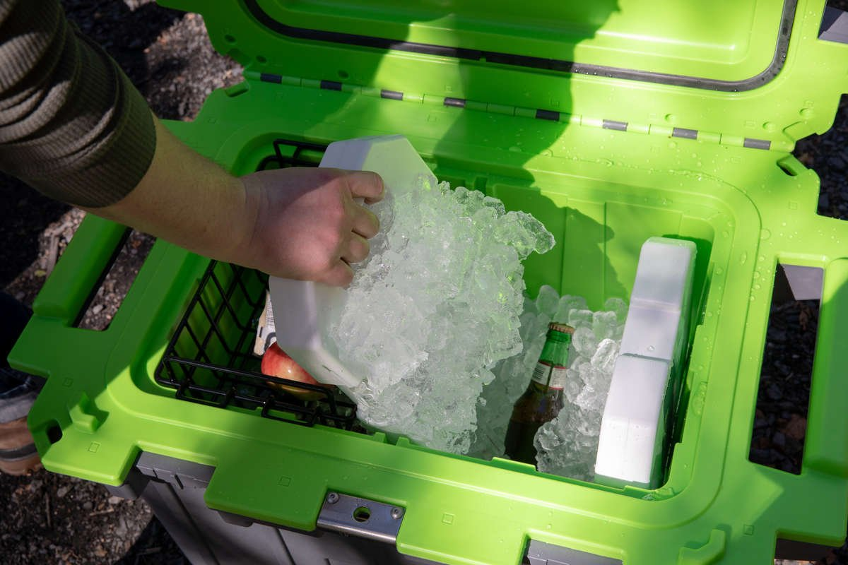 A person pulling a 5lb Pelican Ice pack out of a Pelican Elite Cooler. There is ice frozen all over the reusable ice pack.