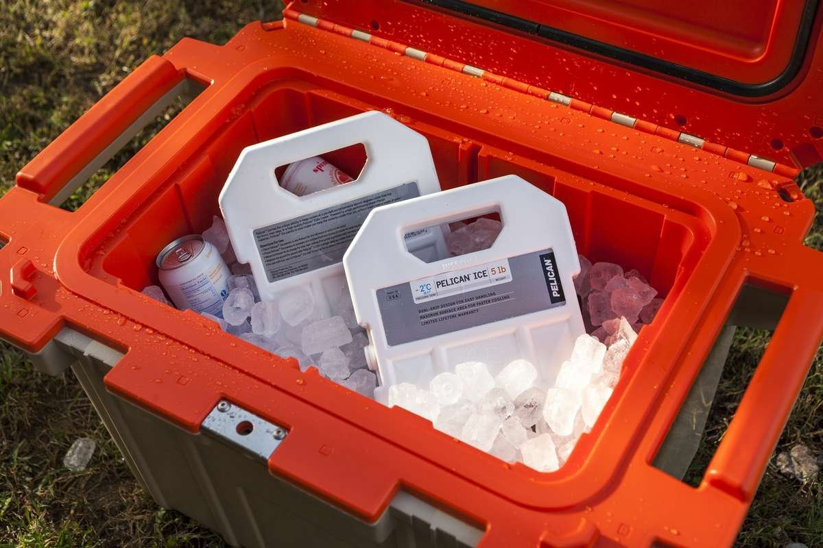 An open Pelican Elite Cooler filled with drinks, ice and two 5lb Pelican Ice packs.