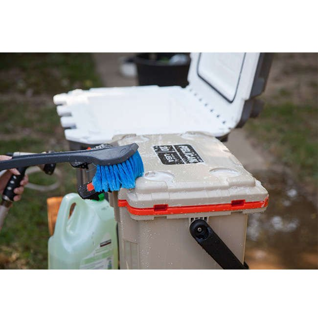 A person cleaning a Pelican Elite Cooler with dish soap and a scrub brush.
