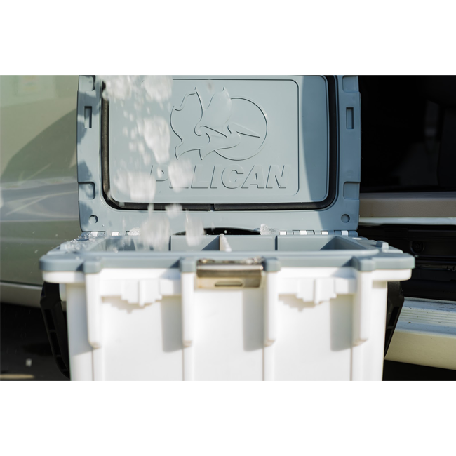 An open Pelican Elite Cooler with ice being poured into it.