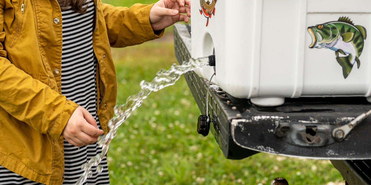 A stream of water pours out of the drain of a Pelican Elite Cooler as a person watches.
