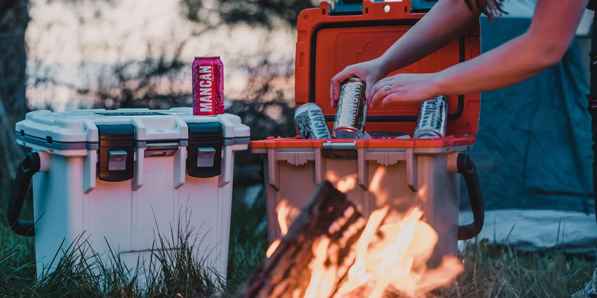 Two Pelican Elite Coolers side by side near a campfire; one is closed and the other is open. A person is pulling a canned beverage out of the ice in the open cooler.