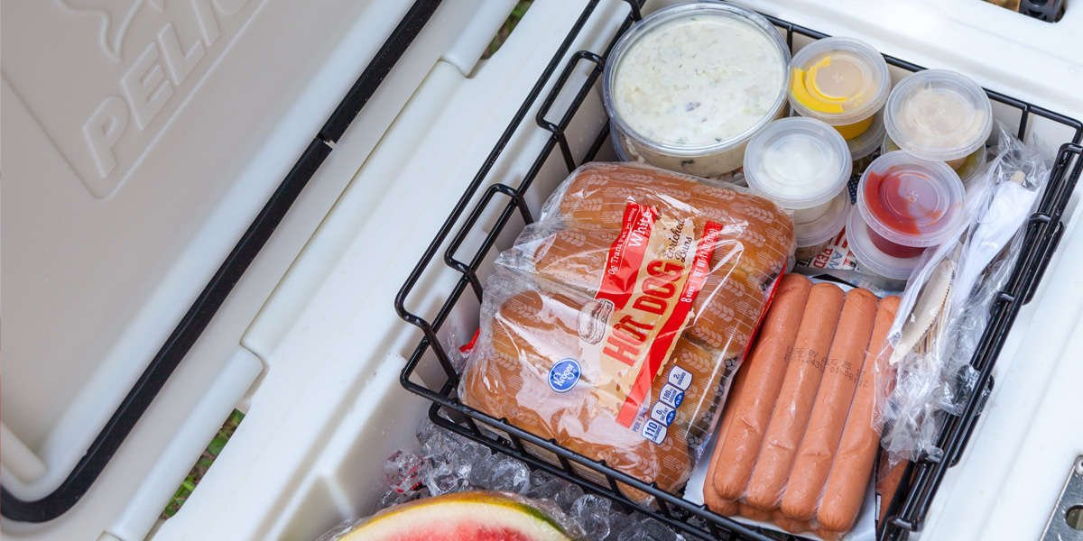 A packed cooler showing how to use a dry rack basket to protect delicate food.