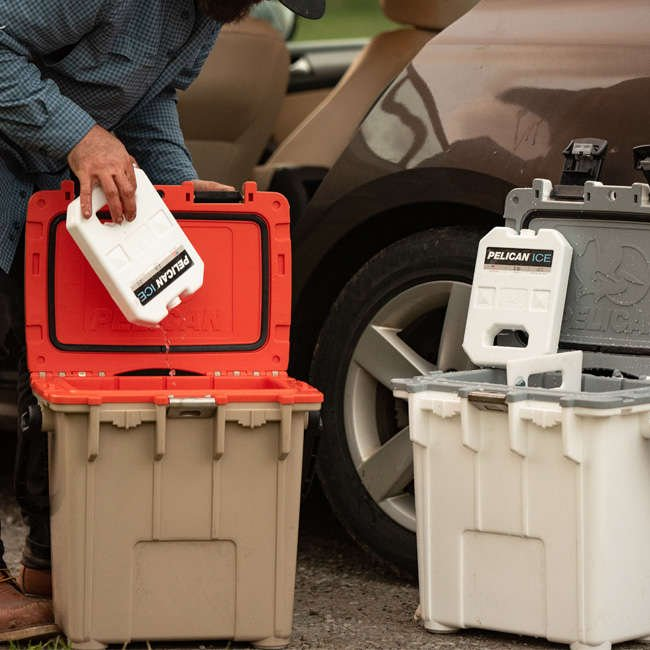 Two Pelican Elite Coolers side by side. A person is putting a 2lb Pelican Ice pack into the cooler on the left.