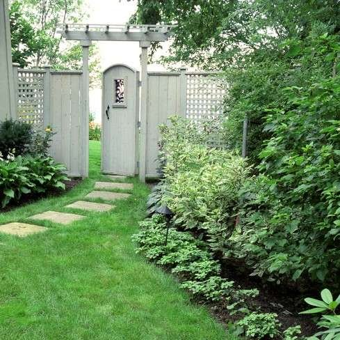 Shade Garden with pathway leading to white fence