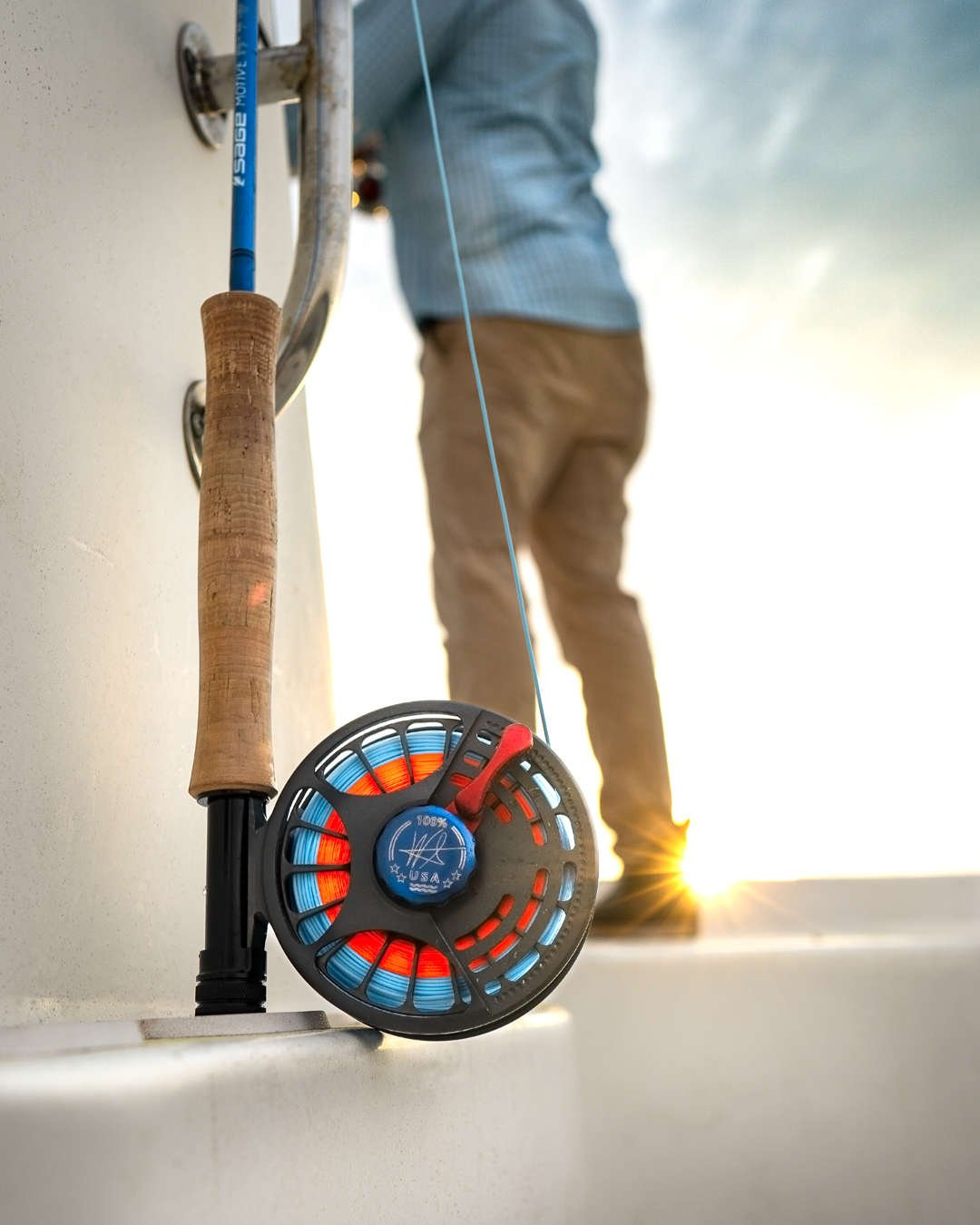 Seigler saltwater fly reel on boat with sun in background.