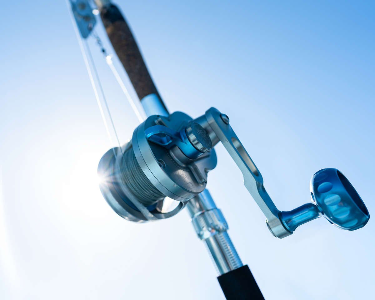 fishing reel and rod with sun in the background.