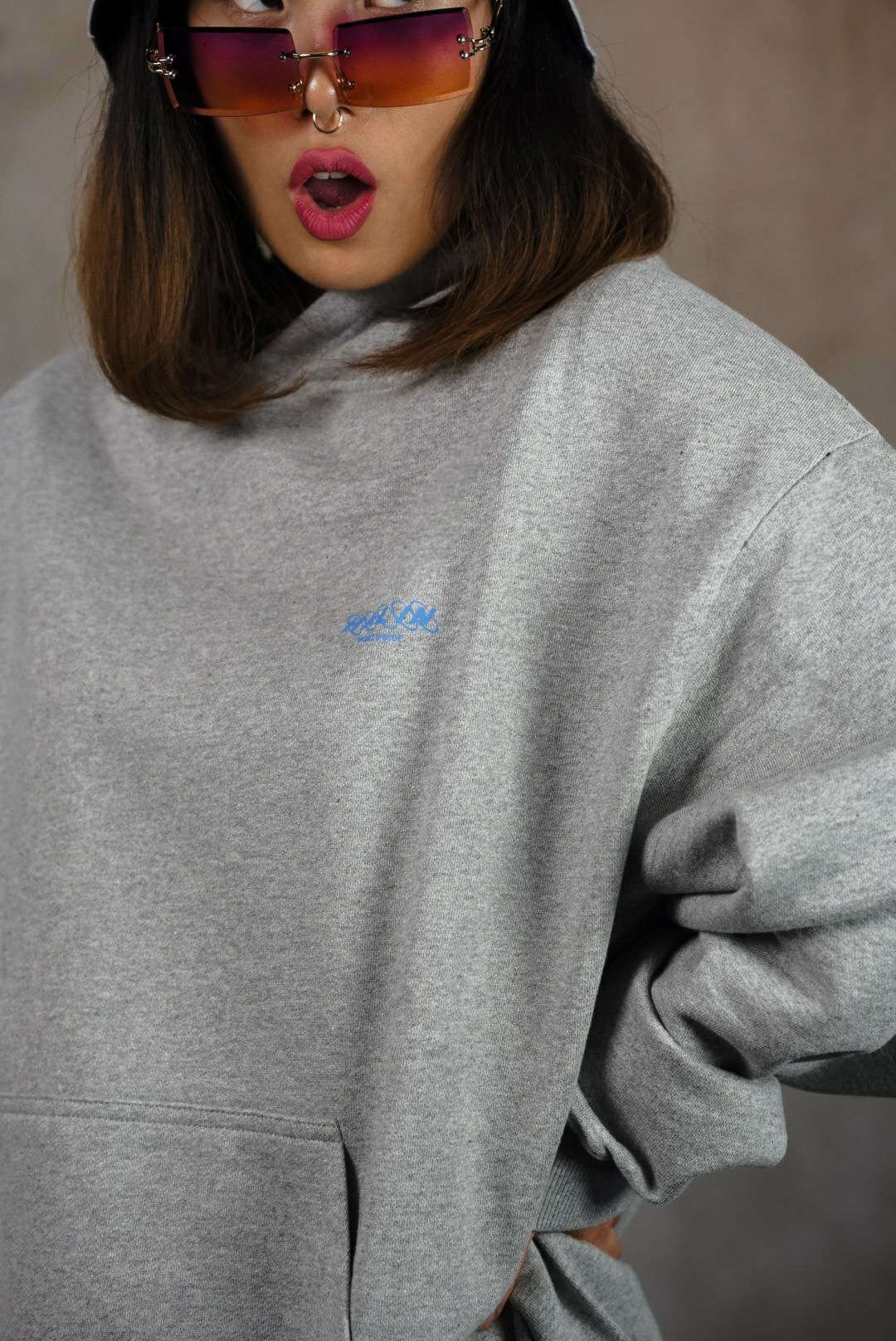 Female streetwear model wearing Halin Bucket Hat and grey oversize hoodie.