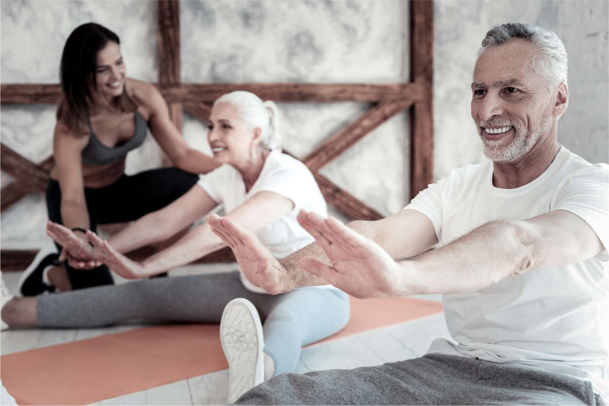 An older couple in their late 60s is stretching their legs on yoga mats with a young yoga teacher assisting them.