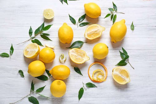 Several lemons some whole others sliced on a plain white table with individual leaves scattered around them.