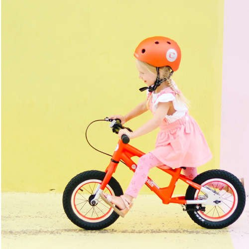 Little girl on an orange balance bike and matching helmet, running