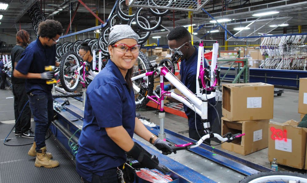 Woman smiling working on a small girls bike on the assembly line.