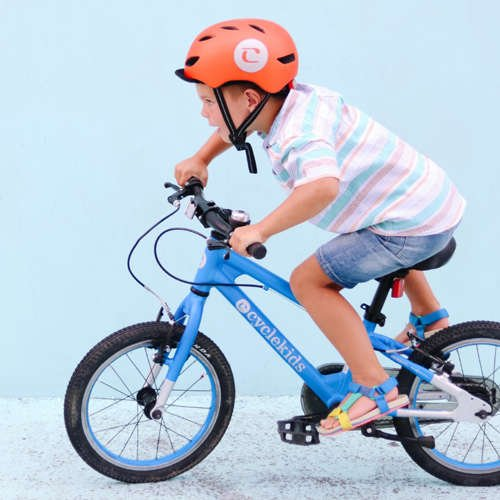 "Small boy on 16"" CYCLE Kid's bike with an orange helmet, leaning forward"