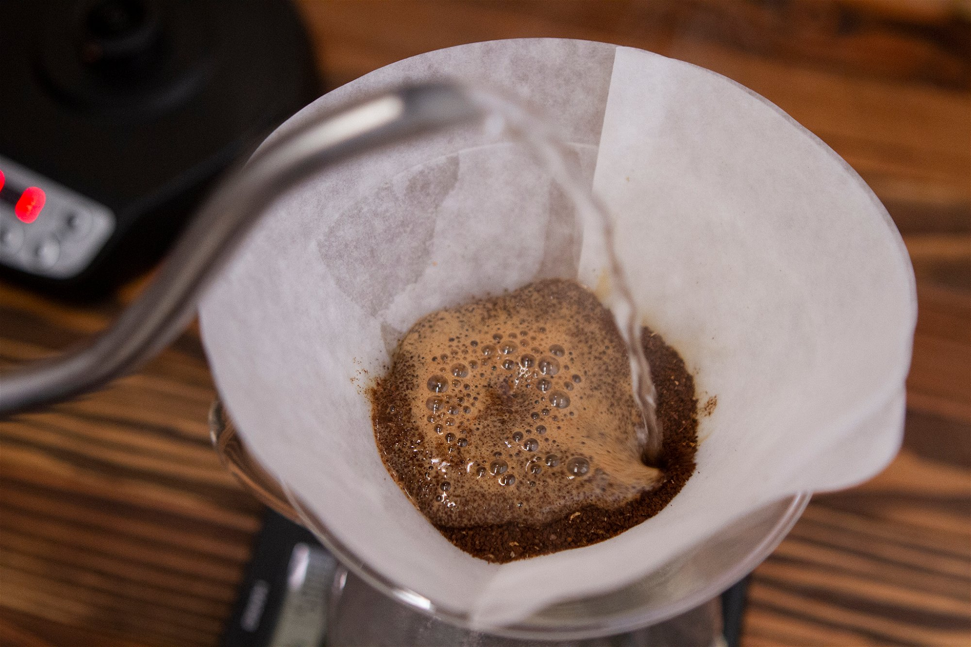 POURING WATER ON TO COFFEE GROUNDS IN CHEMEX