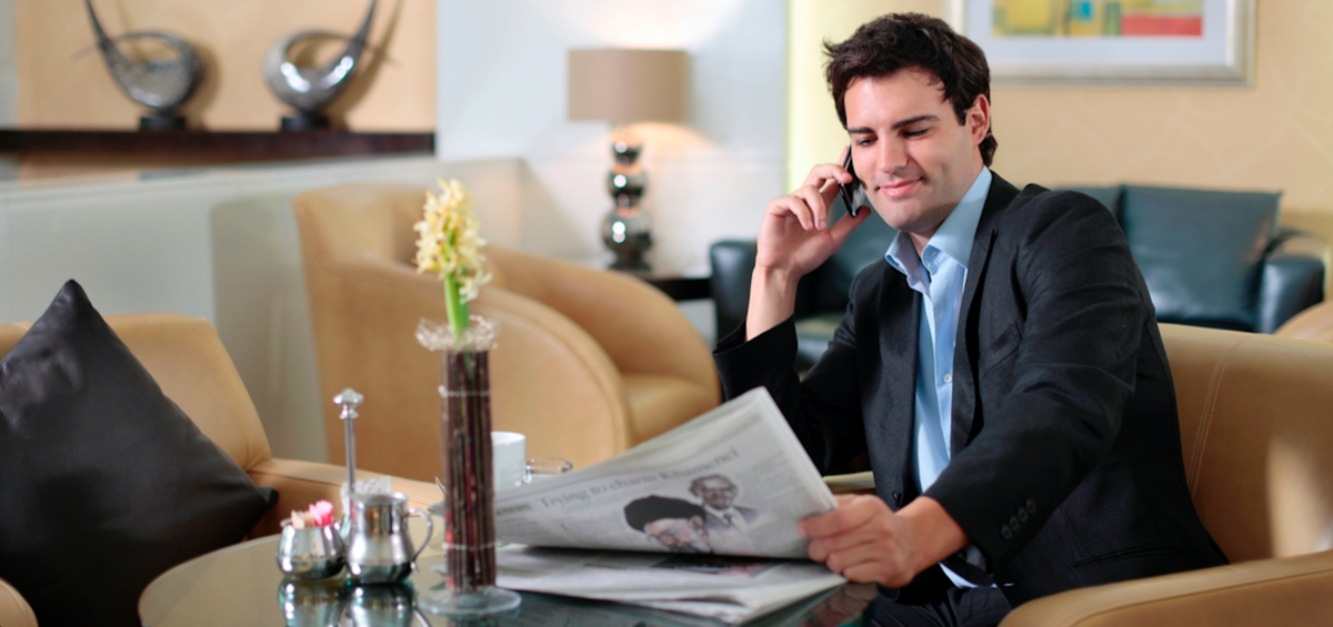 Businessman doing work happy because he has a charged cell phone thanks to bizchargers