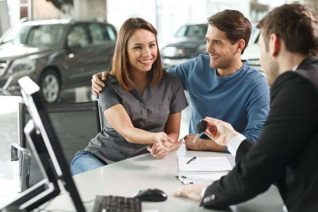 Car dealership salesman offering charger to guest to charge cell phone