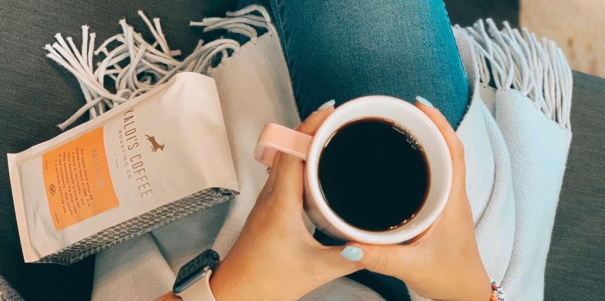 Holding a mug on coffee with a 12oz bag of Kaldi's Coffee