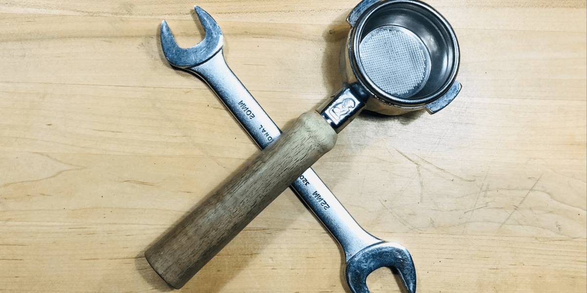 A wrench and an espresso portafilter on a wooden table