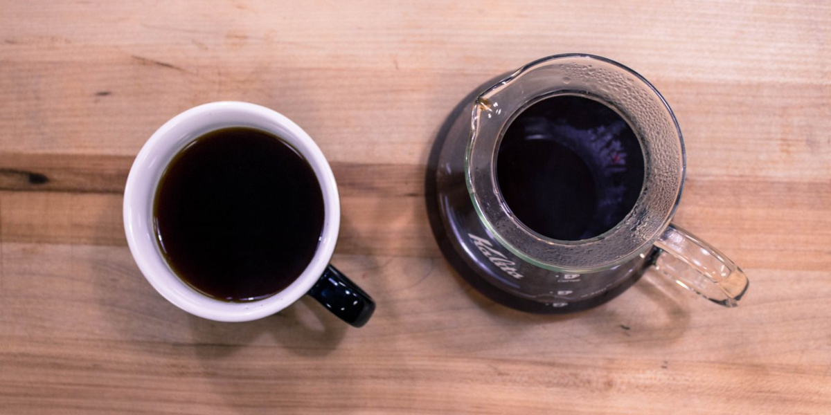 A 12oz mug sitting next to a Kalita decanter filled with coffee