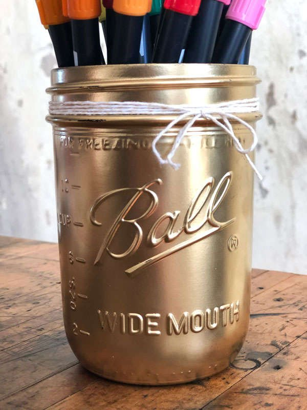 a close up of a metallic gold jar with baker's twine wrapped around the top of the jar