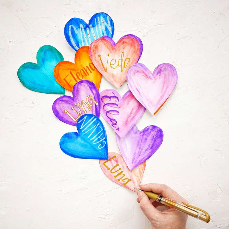 picture of decorated paper hearts laid out to look like balloons with a watercolor effect using Crayola makers and water featuring different names hand lettered on top in gold and white using the uniball gold gel pen and the white posca paint pen