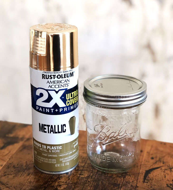 a can of metallic gold spray paint next to a clear simple glass jar