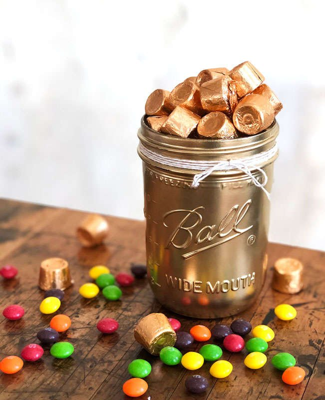 a metallic gold jar filled with gold wrapped chocolates with rainbow colored Skittles scattered around the jar