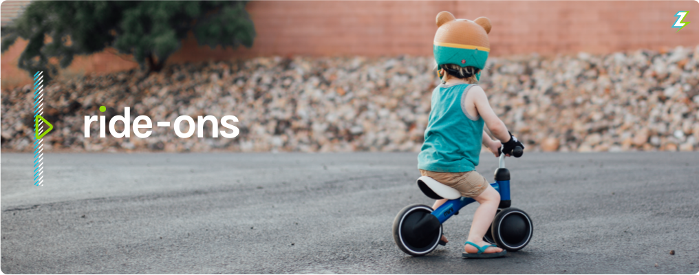 Ride-Ons | Little boy with a bear helmet on a blue Mini riding along a pavement area