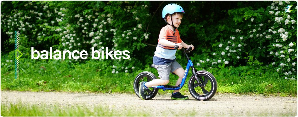 Balance Bikes - Excited toddler with Bright Blue Multi-Sport Helmet and Blue Kazam Pro with Magwheels - Riding along a dirt path with beautiful green nature and white flowers along the background