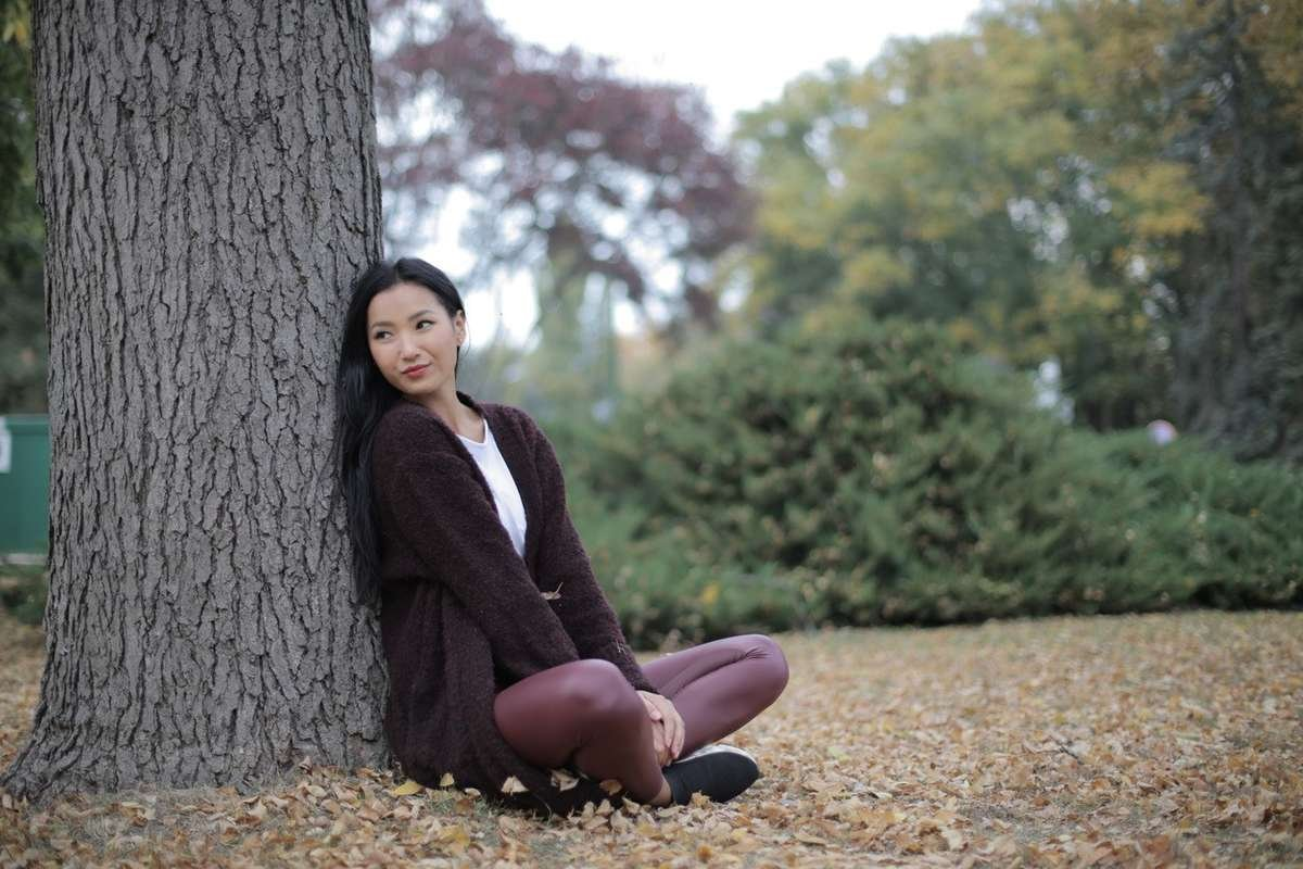 Woman sitting against a tree and relaxing