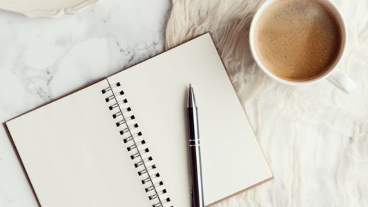 Notebook opened to clean page with pen and coffee