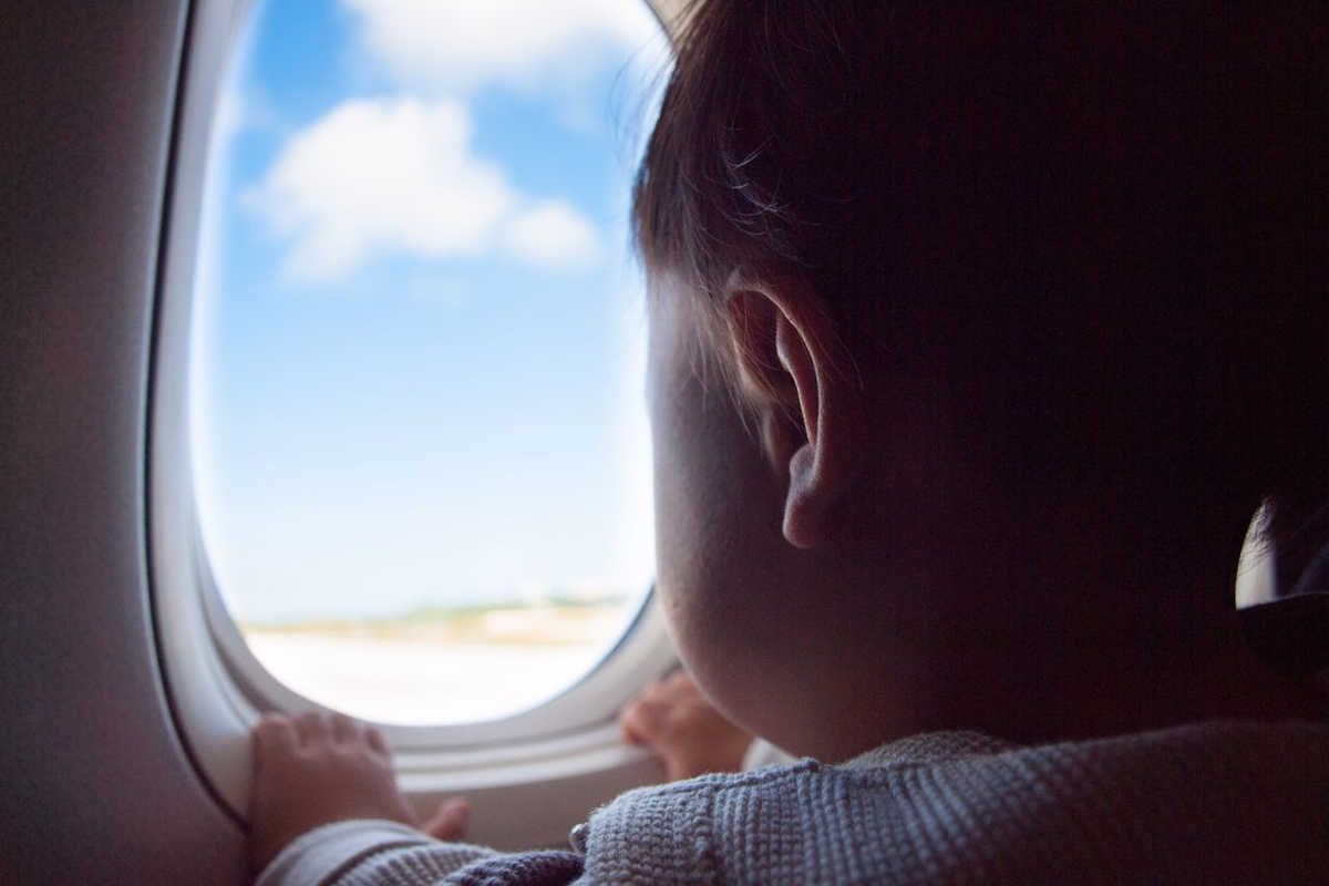 Child Gazing Out of Airplane Window