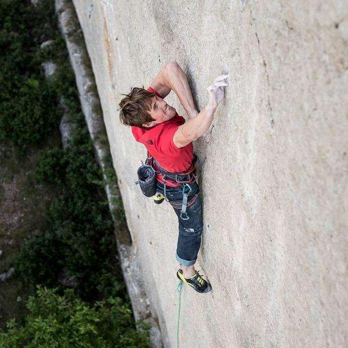 James Pearson mid climb on a barren wall